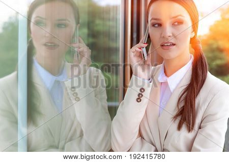 Beautiful businesswoman answering cell phone by glass door