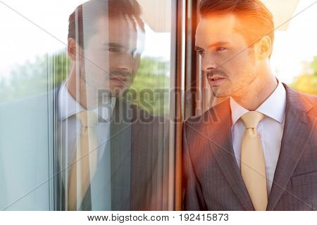 Thoughtful businessman leaning on glass door