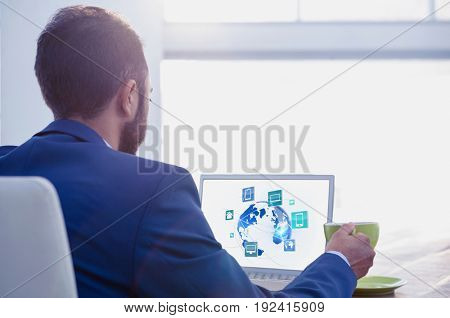 Digital composite of businessman at desk with laptop