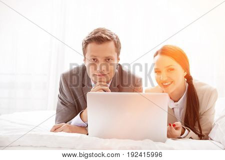 Portrait of happy business couple with laptop in hotel