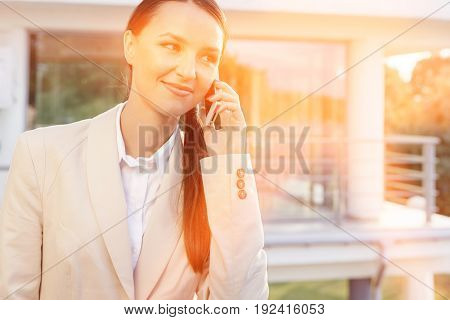 Beautiful businesswoman answering cell phone against office building