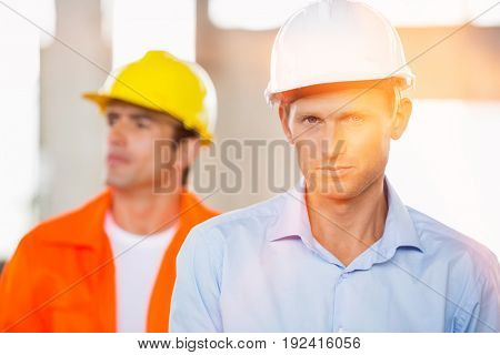 Portrait of confident male architect at construction site with coworker in background