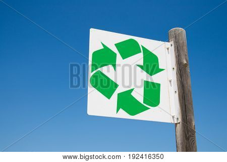 Recycling sign at the beach with blue sky