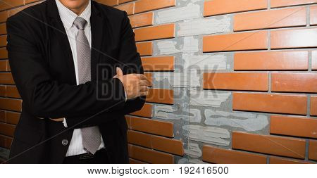 Male model in a suit posing on brick background