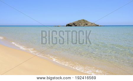 View on the beach Chia with crystal sea water and golden sand in Sardinia Italy.