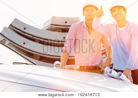Architects with blueprints on car discussing at construction site