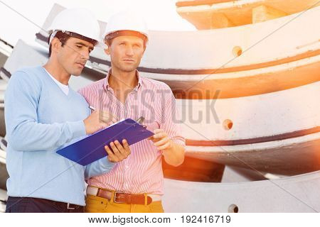 Architects with clipboard working at construction site