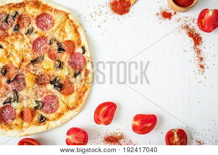 Delicious pizza with ingredients and spices on white rustic background. Flat lay, top view.