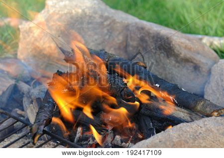 close on flame of campfire between stones on the grass