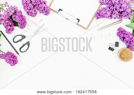 Workspace on white background with clipboard, notebook, scissors, lilac and accessories. Flat lay, top view
