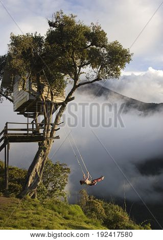 Swing over the abyss with an active volcano in background in Ecuador
