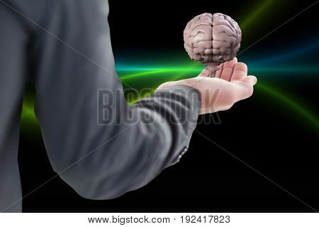 Digital composite of Business man holding a brain on his hand against black background