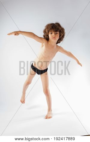 Little curly-haired boy in shorts showing posture swallow. Gray background.