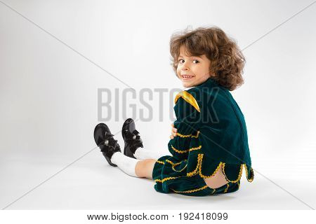 Cute curly-haired boy in the image of the prince sits and stares into the camera. Gray background.
