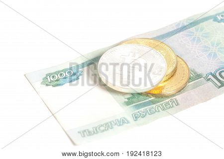 Three Bitcoin on one thousand russian rubles banknotes isolated on white