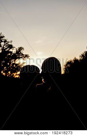 A kiss at sunset. Kissing silhouettes on sunset sky background.