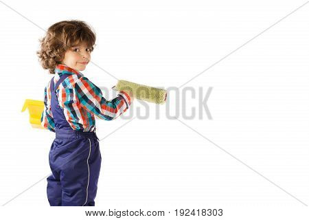 Little curly boy holds a tray in hand he paints the wall roller and looking at the camera. White background.
