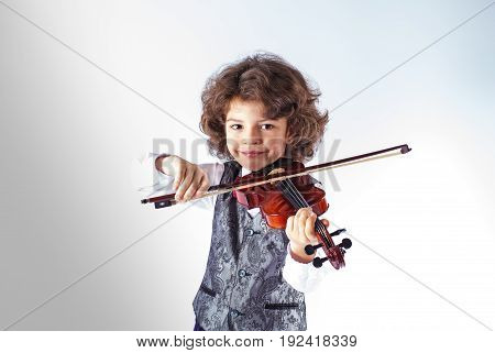 Curly cute boy in a vest playing the violin and looking at the camera. Gray background.