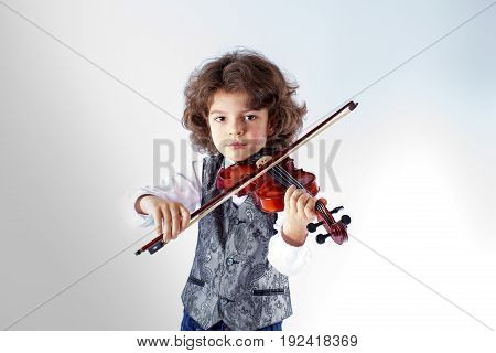 Curly cute violinist waistcoat in playing the violin and looking at the camera. Gray background.