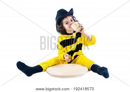 A cute boy in a bee costume drinks from a mug. White background.