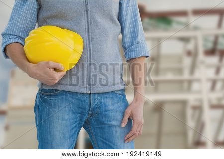 Digital composite of Worker holding a yellow helmet against construction
