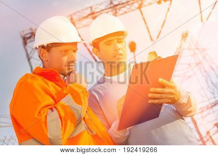 Low angle view of architects discussing over clipboard