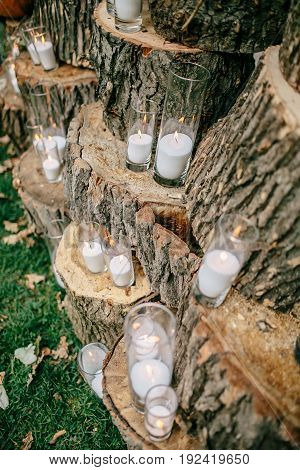 Wedding decorations in rustic style. Outing ceremony. Wedding in nature. Candles in decorated goblets. Selective focus.