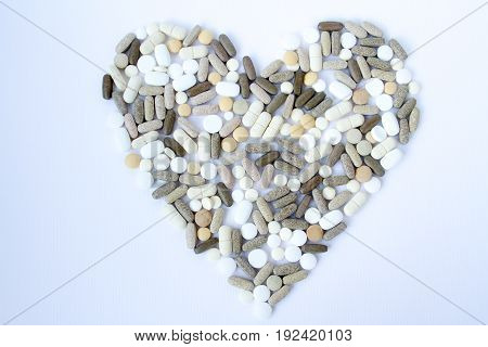 Colorful medical pills loose in the form of heart on a white background.