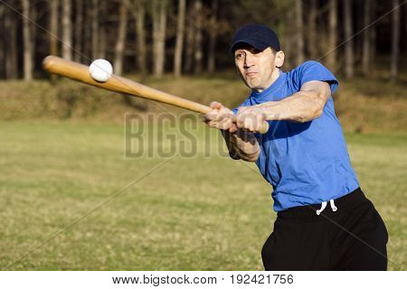 The baseball player is shooting the ball outdoors.