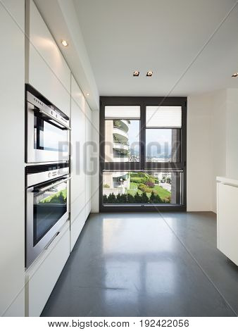 Oven detail and windows in white kitchen. Nobody inside
