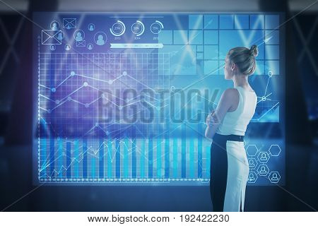 Side view of attractive young woman looking at digital business screen in blurry interior. Future concept. Double exposure