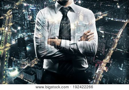 Businessman with folded arms on night city background. Research concept. Double exposure
