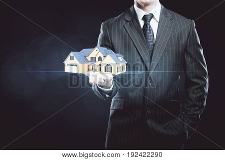 Businessman holding abstract house miniature on dark background. Mortgage concept
