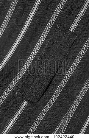 Blank black clothes label on black and white striped cloth