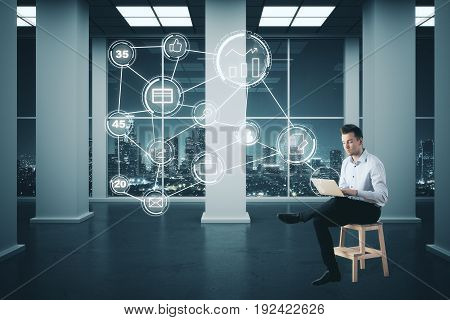 Young businessman sitting on chair and using laptop with digital business icon diagram in interior with night city view. Future concept. 3D Rendering