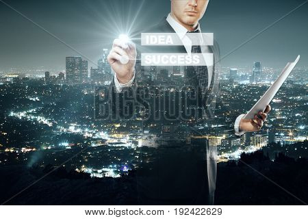 Businessman with document in hand drawing digital business scheme on illuminated night city background. Idea concept. Double exposure