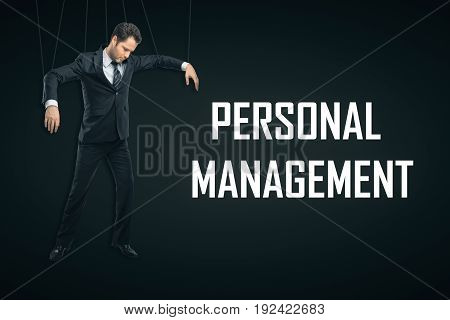 Male puppet on dark background with text. Personnel management concept