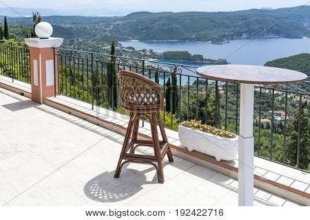 Empty chair and table with a wonderful view of the Paleokastritsa coast. Corfu island, Greece.
