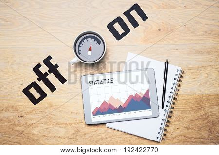 Top view of wooden office desktop with business chart on tablet screen notepad pen and coffee cup with on/off scale. Energy concept