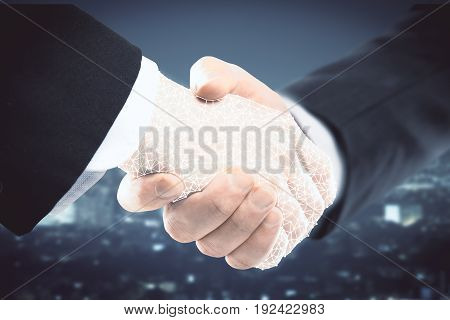 Abstract polygonal handshake on blurry night city background. Partnership concept