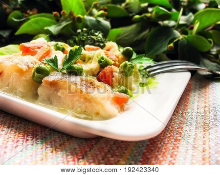 Stew with cod fish fillet with broccoli, carrot, green peas on a plate, selective focus