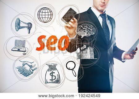 Handsome young businessman with document in hand drawing creative SEO sketch on light background. Search engine optimization concept