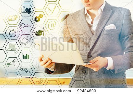 Young businessman in suit holding laptop on bright blurry background with business icons in cells. Success concept. Double exposure