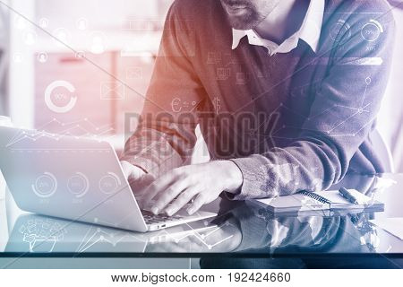 Close up of young businessman using laptop computer in modern office with digital business pattern. Communication concept. Double exposure