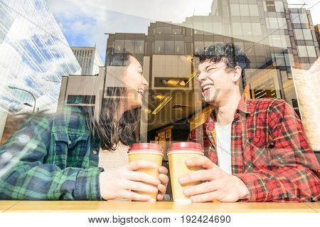 Portrait of a young attractive tourist couple behind coffee bar window. Two best friends having together fun in London drinking cappuccino. Boy and girl with glass reflection of buildings and skyline.