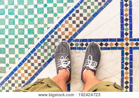 Feet selfie from upper view of man traveler in sneaker during a tour trip around the world. Souvenir photo of multicolor museum floor made of small tiles. Tourist take a photo of his own leg.