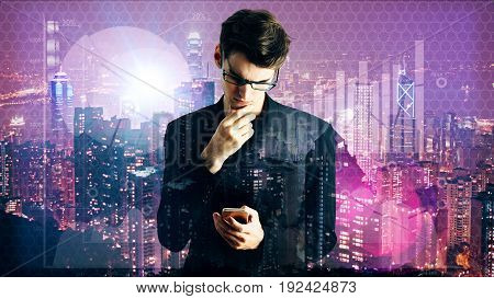 Businessman using smartphone on bright night city background with business charts. Communication concept. Double exposure