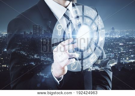 Businessman pointing at circular digital business diagram on nigth city background. Touchscreen concept. Double exposure