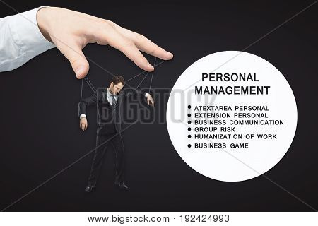 Hand manipulating man puppet on dark background with text