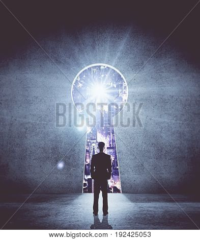Back view of young businessman standing in concrete interior with keyhole opening and illuminated night city view. Accessibility concept. 3D Rendering